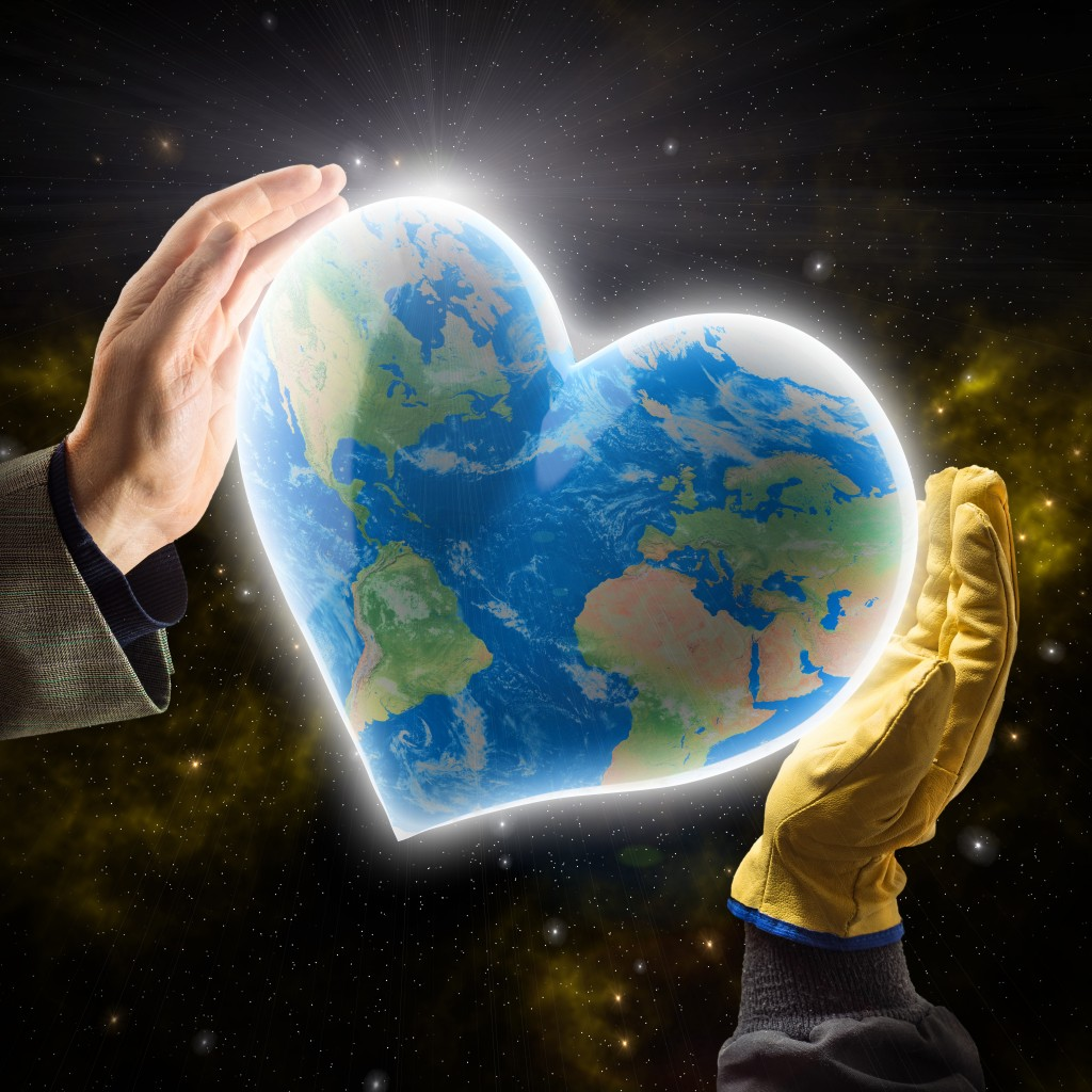 Hands of businessman and worker holding heart-shaped  Earth